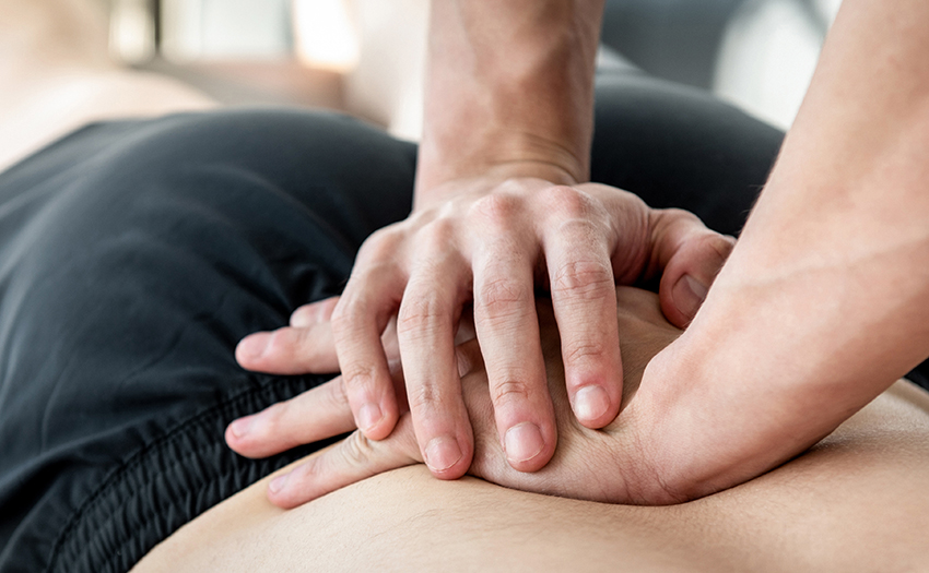 Therapist giving lower back sports massage to athlete